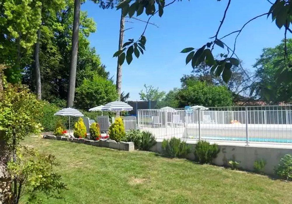 Swimming Pool area with outside seating, sun lounges, overlooked by trees and garden features